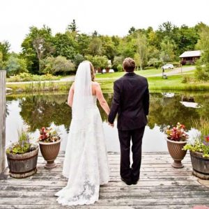 Bride and groom stand by small trout pond