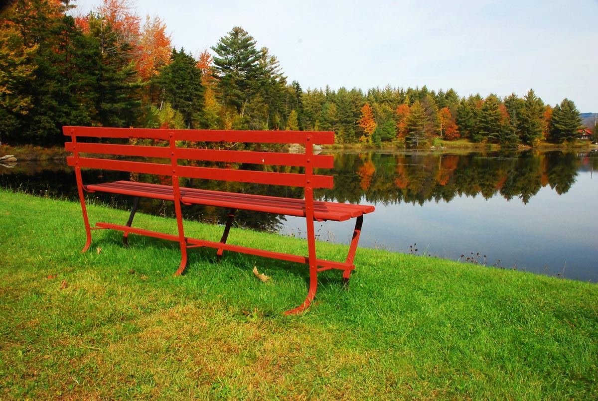red bench looks over fall foliage in vermont at sterling ridge resort
