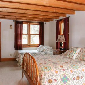 Pond House downstairs bedroom with two beds | Sterling Ridge Log Cabin Resort