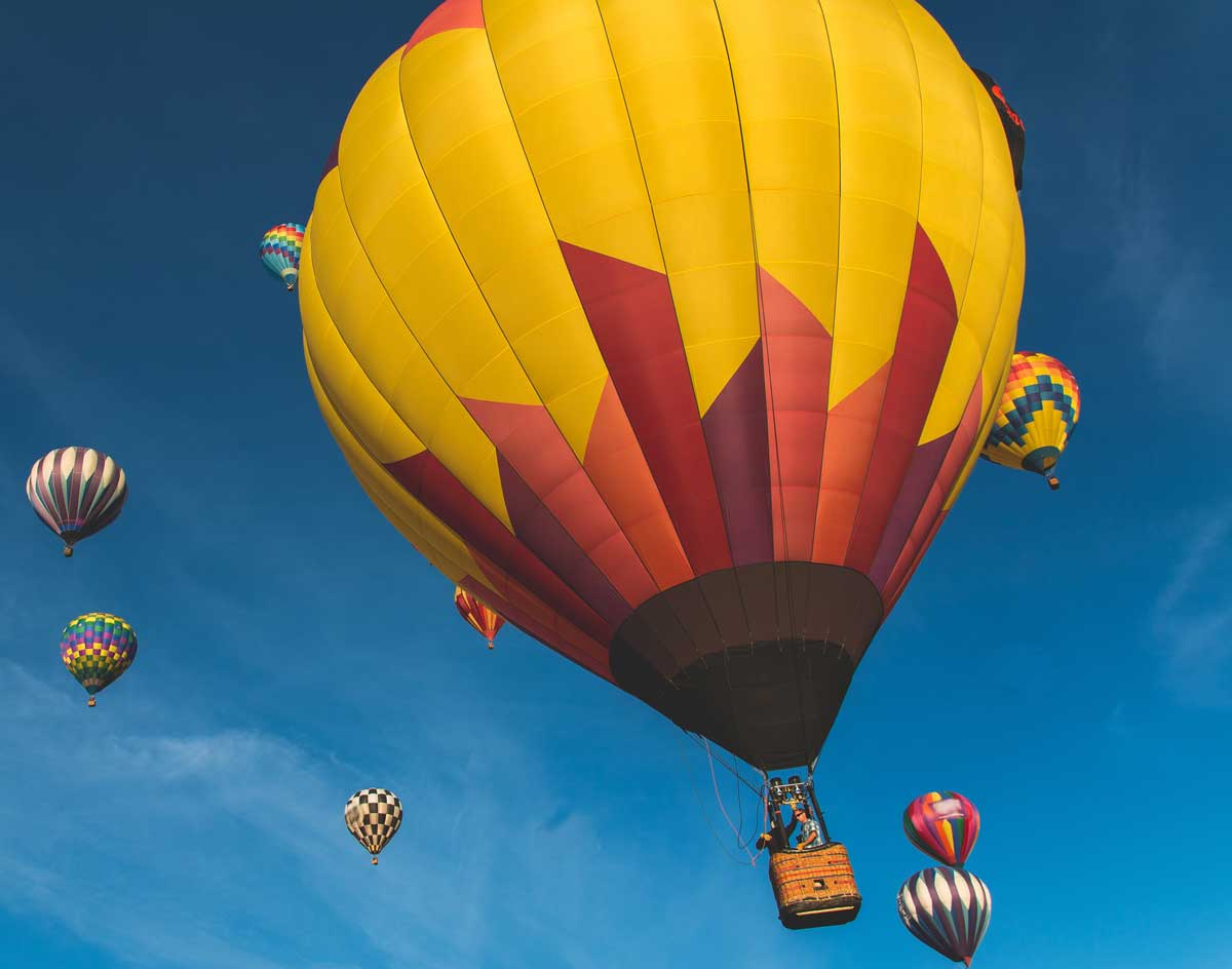 colorful hot air balloons in a blue sky