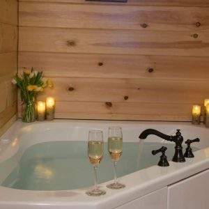 Romantic whirlpool tub with champagne and candle lit | Sterling Ridge Log Cabin Resort