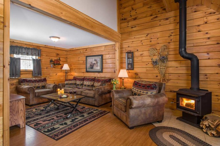living room of 3 bedroom wilderness cabin with fire in woodstove at Sterling Ridge Resort