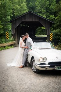 bride and groom by vintage car & vermont covered bridge